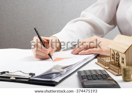 Savings, finances, economy and home budget concept - close up of woman counting at calculator  losses, profit  making notes, working with statistics, analyzing financial results - stock photo