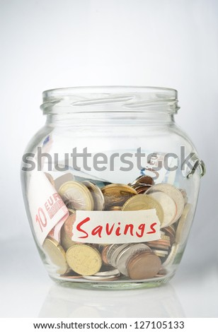 Savings jar full with coins - stock photo