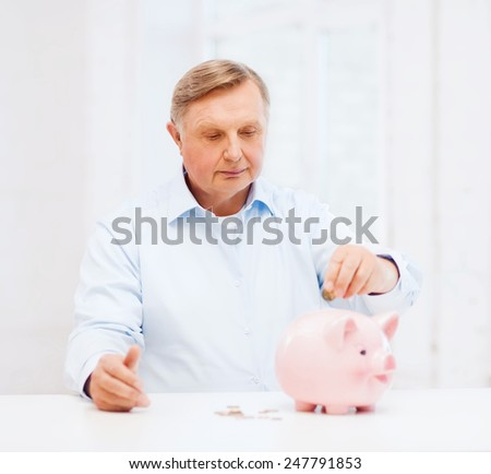 savings, oldness,business and banking concept - old man putting coin into big piggy bank - stock photo