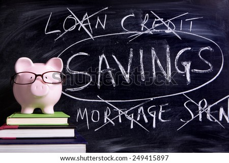 Savings plan : Pink piggy bank with glasses, blackboard with savings plan message.  - stock photo