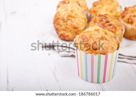 Savory cheese and bacon muffins on the white wooden table - stock photo