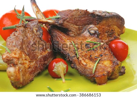 savory plate: grilled ribs over green with peppers and green salad - stock photo