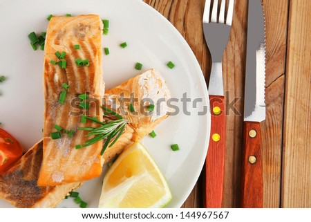 savory sea fish entree : roasted salmon fillet with green onion, red cherry tomatoes pieces, glass pepper grinder, rosemary twigs and lemon on wooden board - stock photo