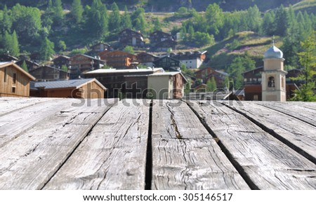 Savoy village bordering the boards of a wooden bridge - stock photo