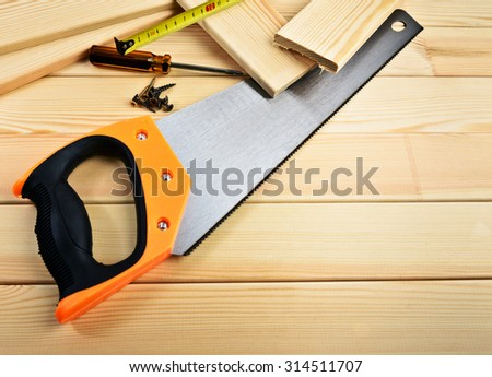 Saw, screw, tape measure and hammer on wood - stock photo