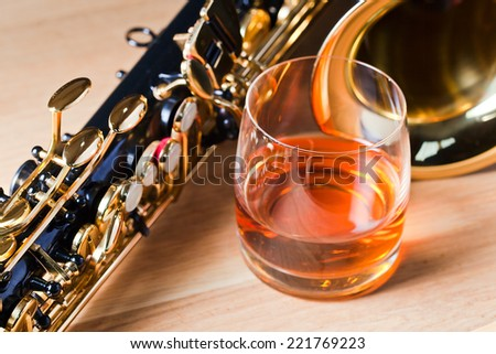 Saxophone and whiskey on a wooden table - stock photo