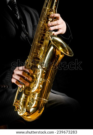 saxophone in male hands on a black background - stock photo