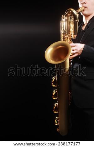 Saxophone jazz music instrument Saxophonist with Baritone sax closeup on black - stock photo