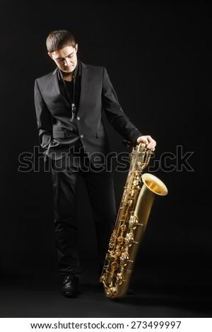 Saxophone player Jazz man Saxophonist with baritone sax musician - stock photo