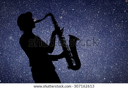 Saxophonist. Woman playing on saxophone against the background of starry sky - stock photo