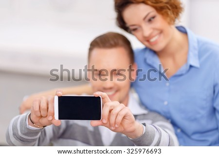 Say cheese. Close up of mobile phone in hands of pleasant handsome cheerful man holding it and making photos with his girlfriend - stock photo