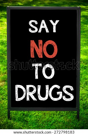 SAY NO TO DRUGS  message on sidewalk blackboard sign against green grass background. Copy Space available. Concept image - stock photo