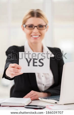 Saying yes to you. Cheerful mature woman in formalwear stretching out paper with yes on it while sitting at her working place - stock photo