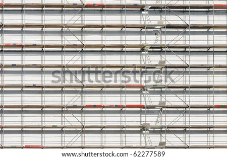 Scaffold against white wall. Can be used as background. - stock photo