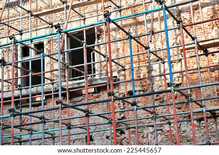 Scaffolding around a brick building renovating facade - stock photo