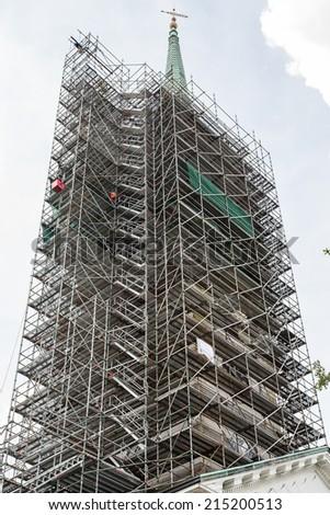 Scaffolding around a massive old church steeple - stock photo