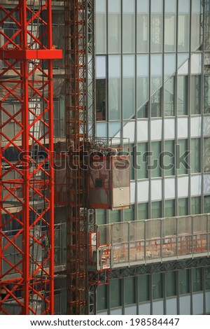 Scaffolding crane with lift on a building under construction - stock photo