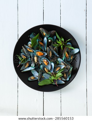 scald mussel with thai sweet basil in black plate - stock photo