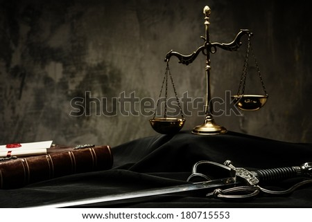 Scales, book and Sword of Justice on a judge's mantle - stock photo