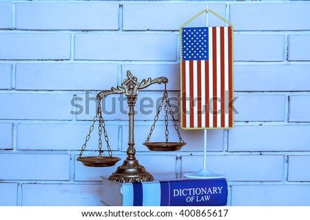 Scales of Justice, american flag, dictionary of law on the brick wall background, BLUE TONE - stock photo