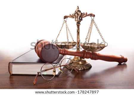 Scales on chains, book, glasses, judges gavel on the table - stock photo