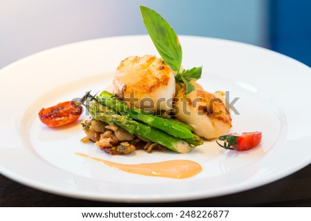 Scalllop with asparagus on plate - stock photo