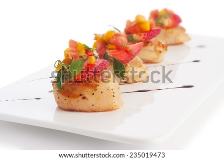 Scallop soaked with fresh yellow mango salsa, on white. - stock photo