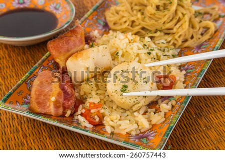 Scallops sauteed with bacon on bed of rice stir fry with Chinese Noodles.  Served in Oriental Design dishes with chopsticks and bowl of soy sauce against bamboo place mat background. - stock photo