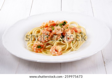 scampi with butter white wine sauce, parsley and spaghetti on a white plate - stock photo