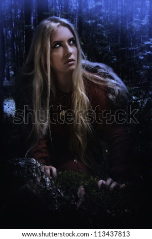 Scandinavian girl in the night dark forest - stock photo