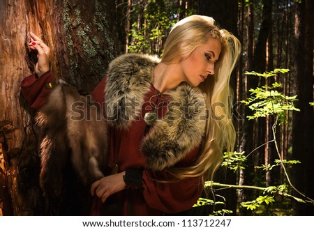 Scandinavian girl with fur skins on a forest background - stock photo