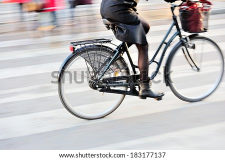 Scandinavian woman on bike. Panning blur. Focus on rear wheel. - stock photo