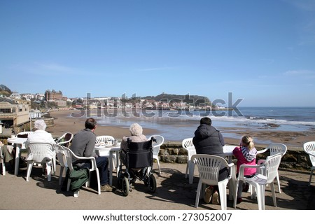 SCARBOROUGH, NORTH YORKSHIRE, UK. APRIL 20, 2015.  Holidaymakers enjoying the view of the South bay whilst having refreshment outside the cliff cafe at Scarborough, North Yorkshire, UK. - stock photo