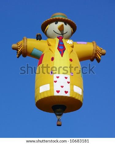 Scarecrow shape hot air balloon over a blue sky - stock photo