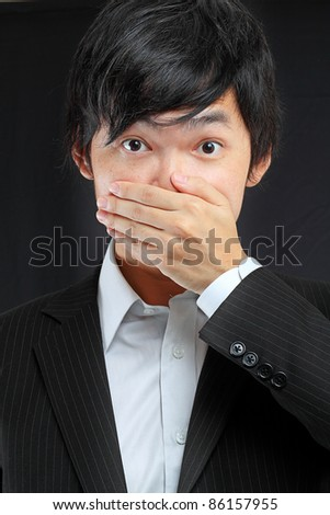 scared adult man with hand covering mouth - stock photo