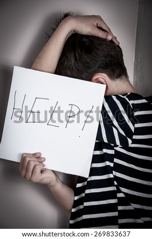 Scared and abused young boy holding the paper with handwritten help sign. Low key - stock photo