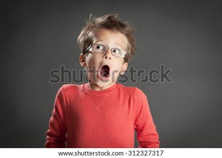 Scared and shocked little boy in glasses. Studio shot portrait over gray background. Fashionable little boy. - stock photo