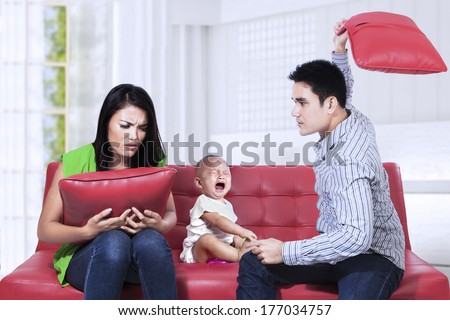 Scared baby sitting on the couch listening to parents argument  - stock photo
