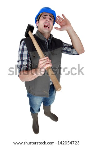 Scared builder cowering away from camera - stock photo