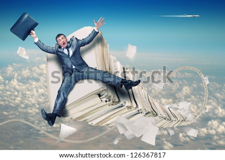 Scared businessman on huge stack of paperwork - stock photo