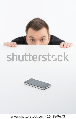 Scared businessman. Terrified young men looking out of the table with mobile phone on it - stock photo