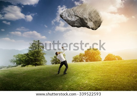 scared businessman under big flying stone over bright landscape - stock photo