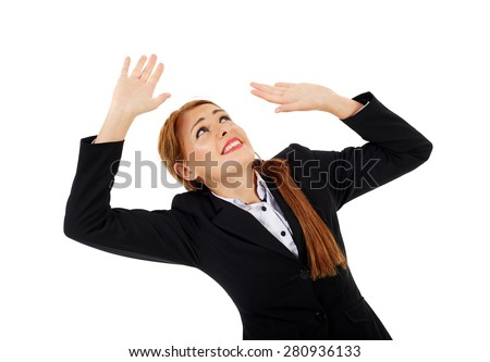 Scared businesswoman getting crushed by an invisible object above, insert your own text or design there - stock photo