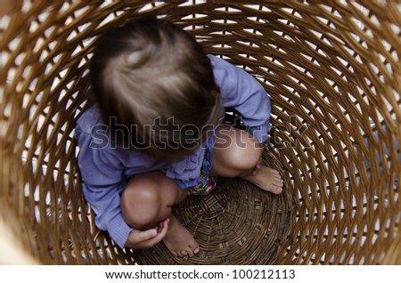 Scared child hides in a laundry basket. - stock photo
