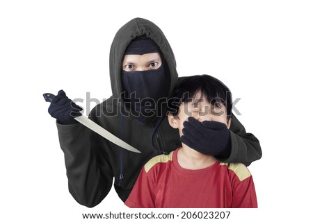 Scared child with an adult man's hand covering her mouth and threatening using a knife - stock photo
