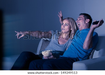 Scared Couple Watching Horror Movie At Home - stock photo