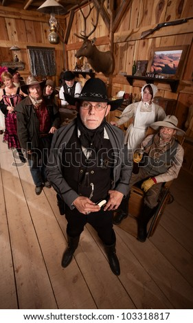 Scared customers behind tough sheriff in old west saloon - stock photo