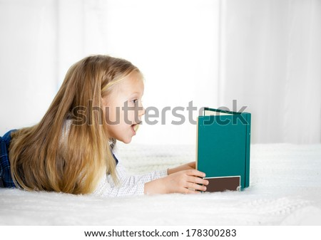 scared cute blonde haired school girl wearing a school uniform reading a book  lying on the bed - stock photo