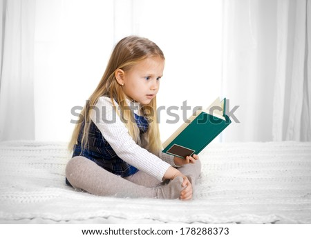 scared cute blonde haired school girl wearing a school uniform reading a book sitting on the bed - stock photo