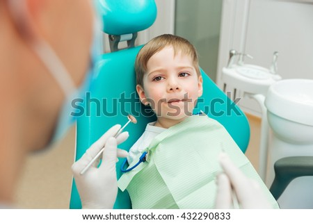 Scared cute little boy sitting with mouth closed in dental clininc - stock photo